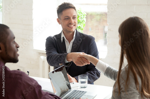 Fotografía  Smiling male worker shaking hand of young female colleague at business meeting,