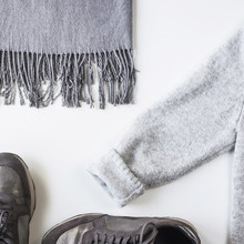 Gray With Silver Female Sneakers, Scarf And Sweater On A White Background. Autumn Fashion Concept. Top View, Flat Lay