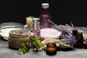 Fototapeta Aromatic composition of lavender, herbs, cosmetics and salt on a dark table top