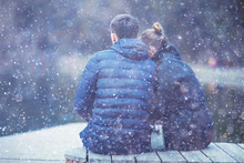 Couple Cuddling On A Bench In Winter