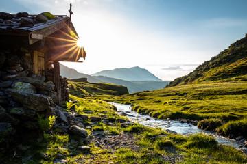 Alm neben einem Bach im Sommer beim Sonnenuntergang