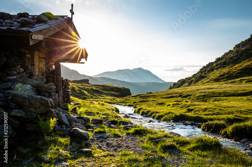obraz lub plakat Alm neben einem Bach im Sommer beim Sonnenuntergang