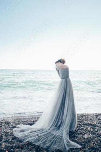 Printed kitchen splashbacks Light blue A woman in a long beautiful dress stands near the sea
