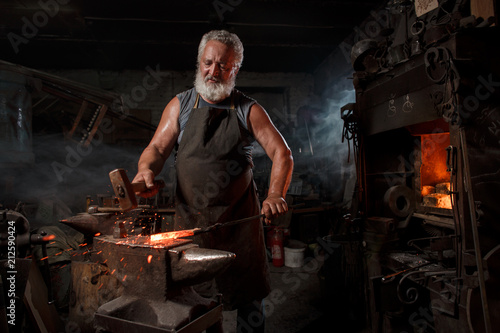 Stampa su Tela Blacksmith with brush handles the molten metal