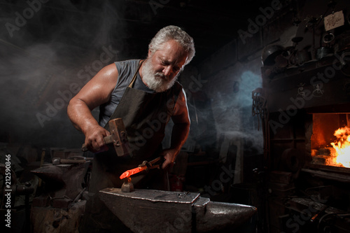 Fotografia Blacksmith with brush handles the molten metal