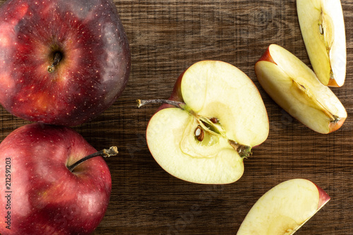Photo Sliced red delicious apples flatlay on brown wood background two whole one half and three slices