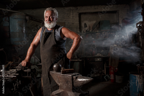 Portrait of a brutal blacksmith artisan in an apron in a blacksmith Wallpaper Mural