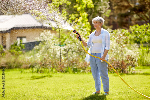 Obraz na plátně gardening and people concept - happy senior woman watering lawn by garden hose a