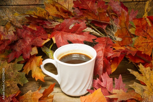 Fotografie, Obraz  A single hot cup of coffee encircled by leaves in autumn colors on a wooden surface with a texture applied to the fringes of the image