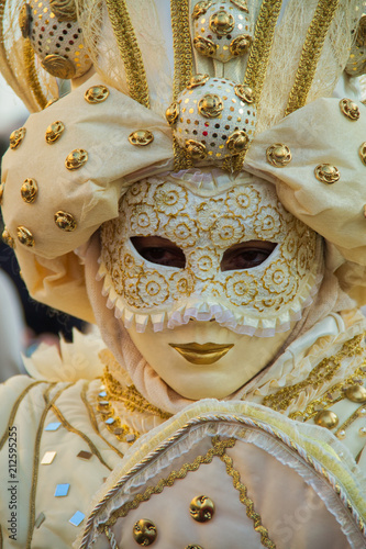 A costumed reveler of the Carnival of Venice in a white and gold costume looking directly at the camera.
