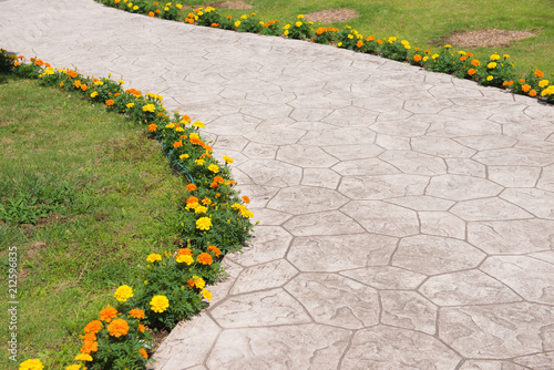 Empty pavement with colorful flowers in the park. Wallpaper Mural