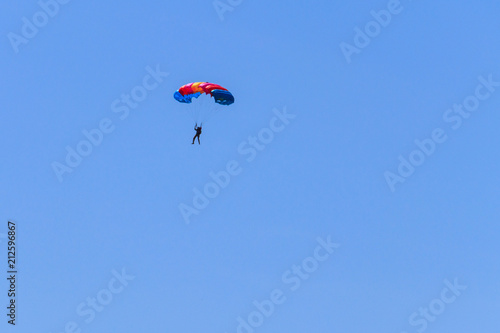 Tuinposter Luchtsport Parachutist descending with a parachute against blue sky
