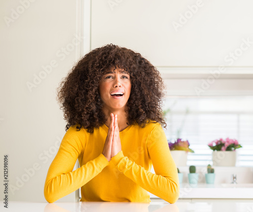 African American Woman Wearing Yellow Sweater At Kitchen Begging And
