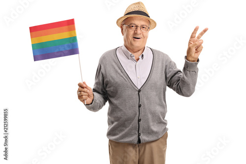 Fotografía Mature man holding a rainbow flag and making a peace gesture
