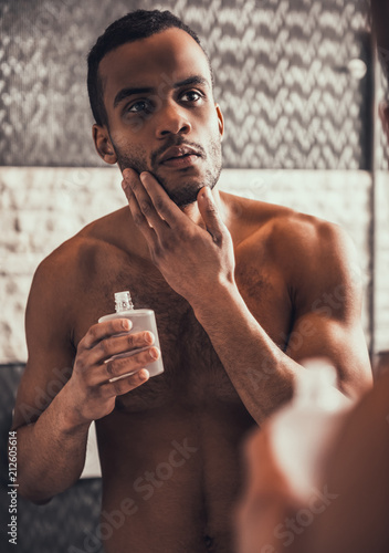 Young Afro-American Man Applying Aftershave Lotion Wallpaper Mural