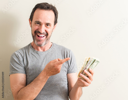 Fototapeta Senior man holding dollar money very happy pointing with hand and finger to the side obraz