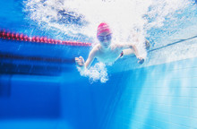 A Little Boy Is Having Fun Under Water, Tumbling And Grimacing, Making Faces