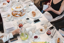 Crop View Of People In Elegant Clothes Sitting At Long White Restaurant Table With Beverages And Pastries On Dessert Stands And Plates From Above