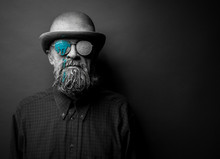 Portrait Of A Bearded Man In With Sunglasses. The Face Is Covered With Clay. On Glasses Green Paint