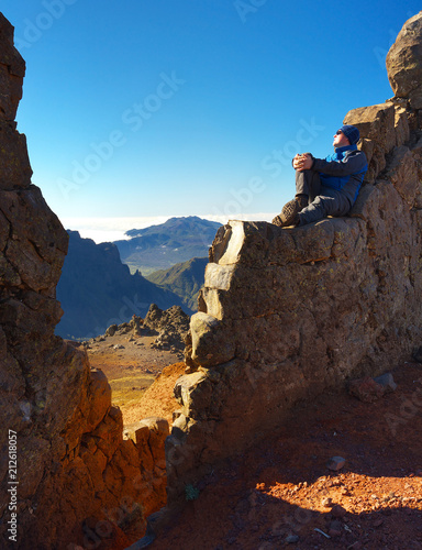 Resting man sitting on the rocky wall above the crater Caldera de Taburiente, Island of La Palma, Canary Islands, Spain