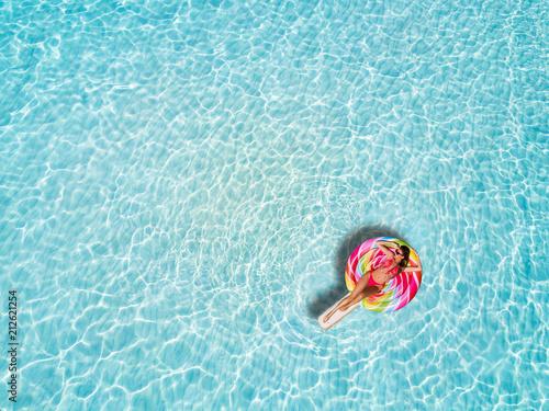 Fotografie, Obraz  Junge, blonde Frau treibt auf einer Lolliförmigen Luftmatratze über die tropisch