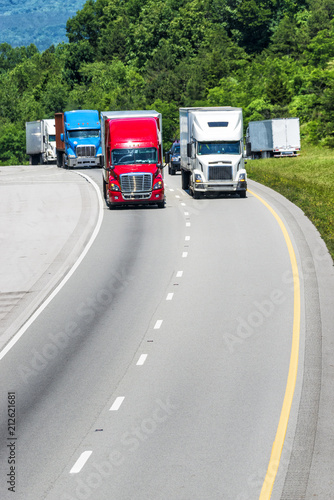 Fotografering  Squadron of Heavy Trucks On Interstate With Copy Space