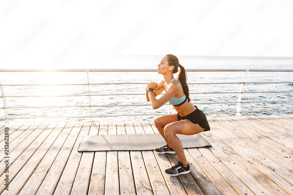 Fototapety, obrazy: Photo of athletic caucasian woman 20s in tracksuit squatting, during workout on boardwalk at seaside