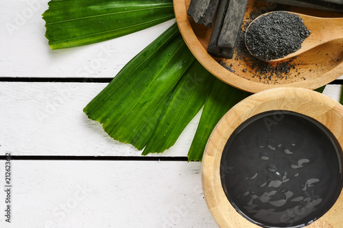 Photo Facial mask and scrub by activated charcoal powder on wooden table