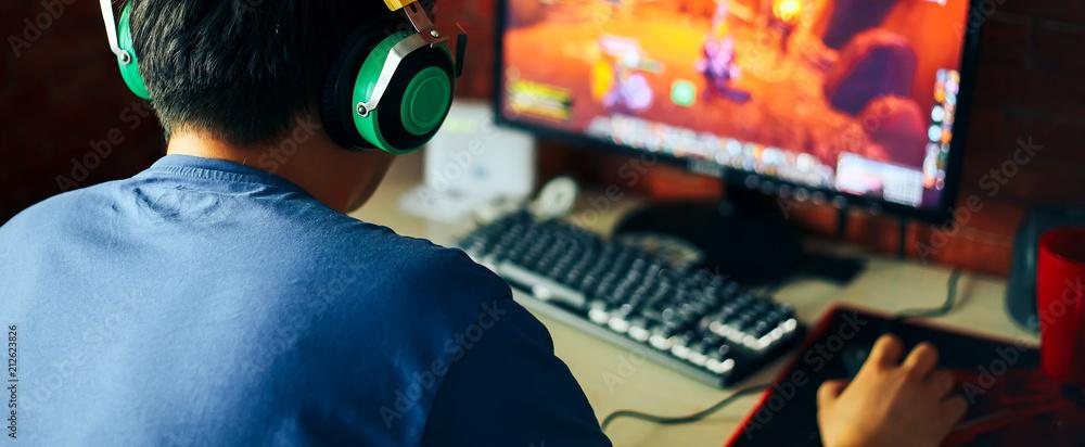 Fototapeta young man playing game on computer, banner