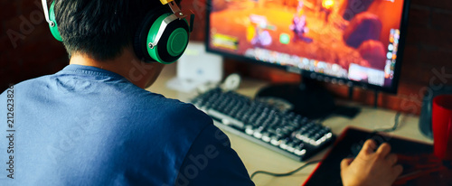 young man playing game on computer, banner Fototapet