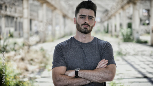 Foto  Handsome young man in empty warehouse, looking at camera and crossing arms on hi