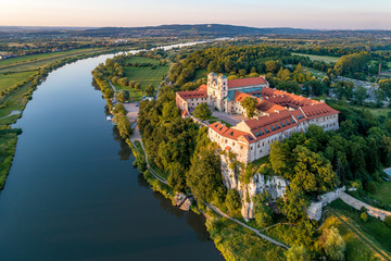 Fototapeta Tyniec near Krakow, Poland. Benedictine abbey, monastery and church on the rocky cliff and Vistula river. Aerial view at sunset. Bielany monastery far in the background