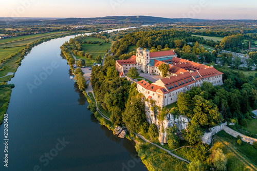 Poster Historisch geb. Tyniec near Krakow, Poland. Benedictine abbey, monastery and church on the rocky cliff and Vistula river. Aerial view at sunset. Bielany monastery far in the background