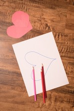 Heart Shape Craft And Colored Pencil On Wooden Floor
