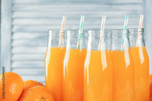 Staande foto Sap Bottles with fresh citrus juice on on blurred background