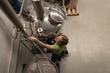 Female worker checking distillery machine