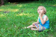 Pensive Baby Boy Sitting On Gr...