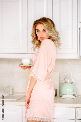 young smiling woman drinking coffee in the morning Poster