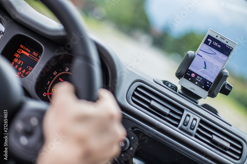 Fotografia  Auto Cockpit von innen, Interieur, Hände am Lenkrad, Smartphone in Handyhalterun