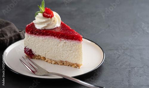 Fotografia, Obraz  Cheesecake slice with fresh raspberries and mint leaves on a white plate