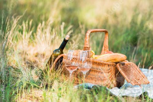 Obraz na plátně wine bottle, basket with loaves on green grass at picnic