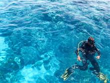 Three Underwater Divers In Bla...