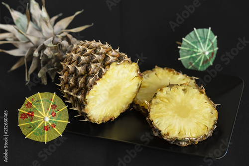 Staande foto Vlees Sliced ripe and yellow pineapple in black plate and decorations for cocktails, umbrellas on dark background
