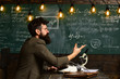 Man sits at table with books and writes. Scientist, teacher and student. Homework or lesson on chalkboard background