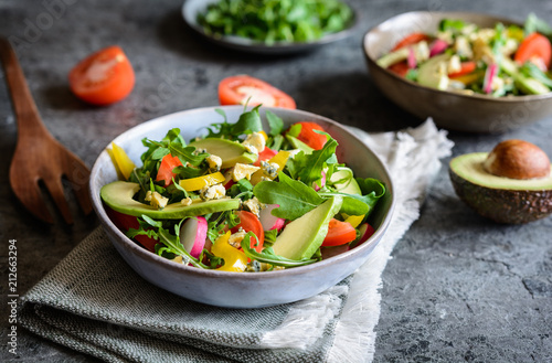 Healthy arugula salad with avocado, radish, bell pepper, tomato and Roquefort cheese
