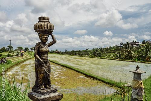 Keuken foto achterwand Asia land Sculpture of woman on green rice fields