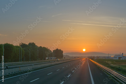 Empty motorway at sunrise, low traffic - Buy this stock photo and