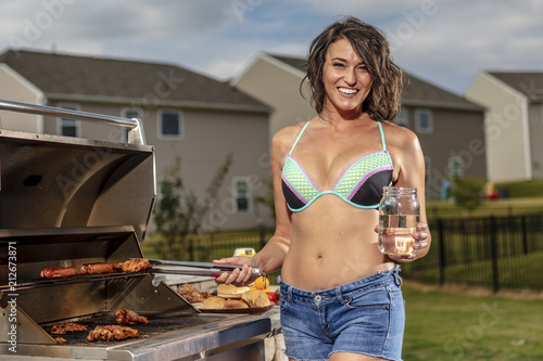 Juliste  A Happy Young Wife Cooking On A Grille Before A Party