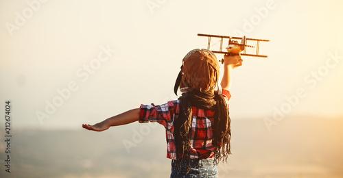 Deurstickers Wanddecoratie met eigen foto Child pilot aviator with airplane dreams of traveling in summer at sunset