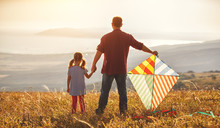 Happy Family Father And Child Daughter Launch  Kite On Meadow